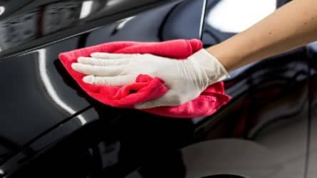 picture of hand wiping a ran across car body