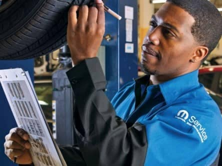 picture of service technician examining a tire