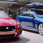Two men securing canoes on roof racks on their Jaguar XE models