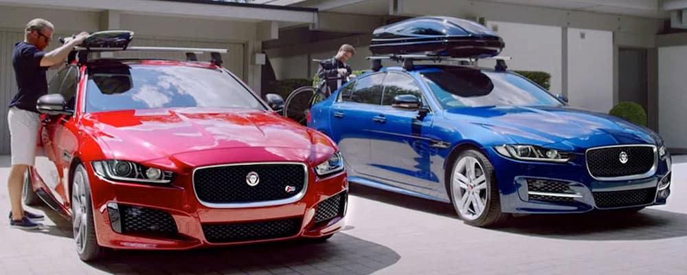 Two men securing canoes on roof racks on their Jaguar XE models