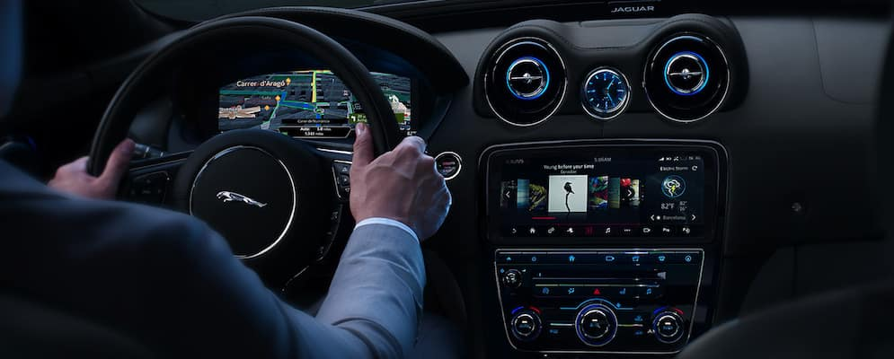 Jaguar XJ interior dashboard with a man's hands on the wheel