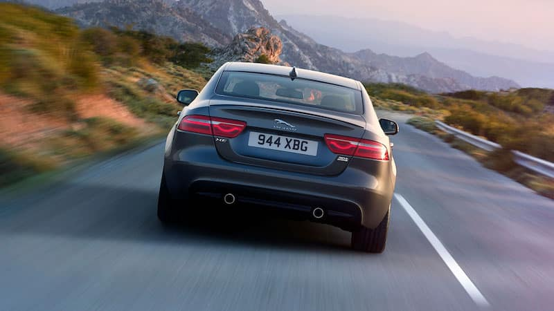 Back view of Silver XE speeding down a road in the mountains