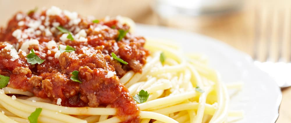 Close up of a plate of spaghetti with red sauce
