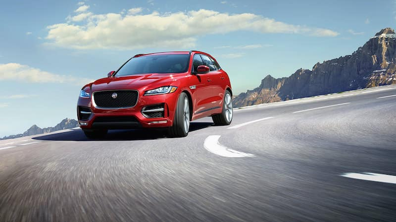 Red F-PACE driving on a road in front of a mountain
