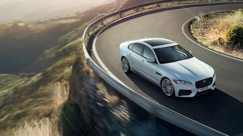 Silver Jaguar XF driving around a curvy road on a mountain