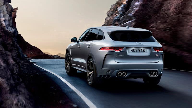 Back view of a silver F-PACE driving through rock formations
