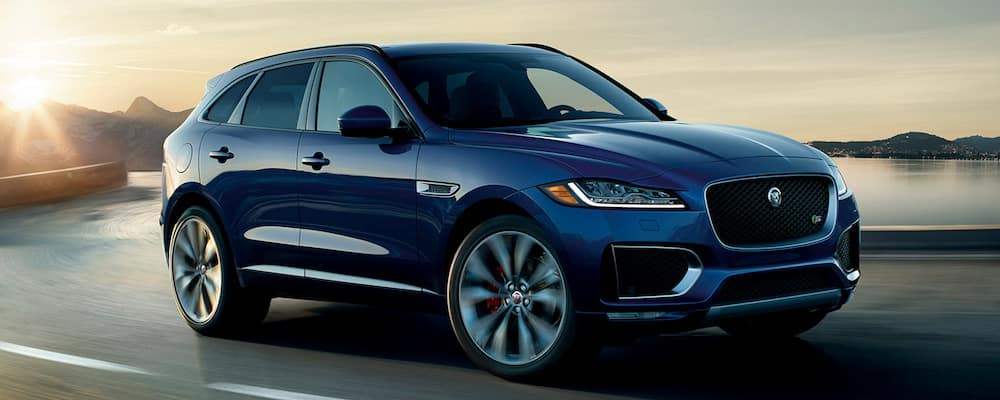 Blue Jaguar F-PACE driving on a road at sunset
