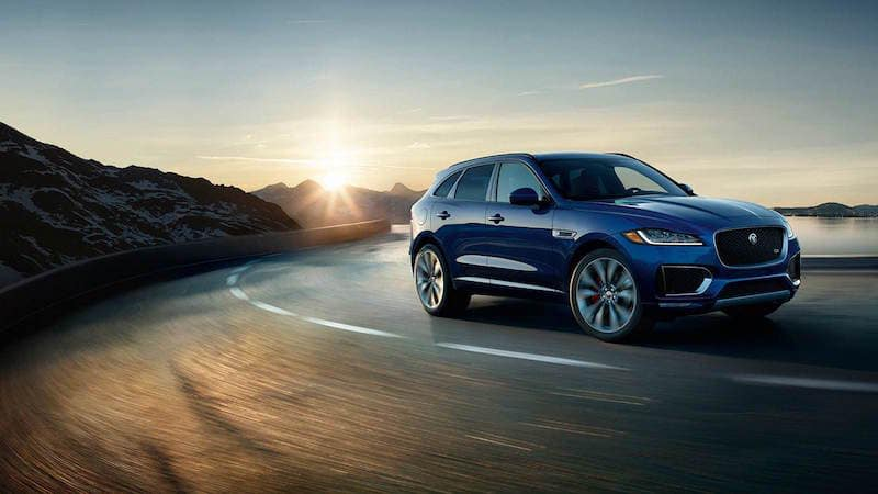 Blue F-PACE driving down a curved road at twilight