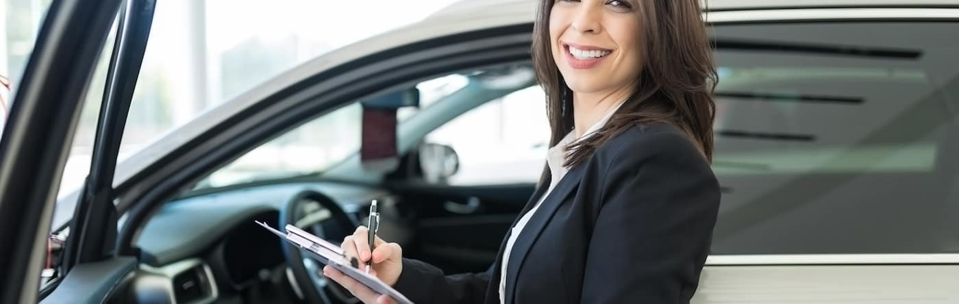 Woman Signing Papers in Front of Car