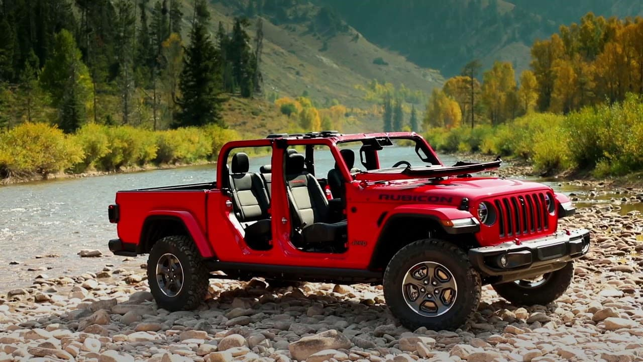 2020 Jeep Gladiator in FireCracker Red outdoors surrounded by Lush Green Mountains