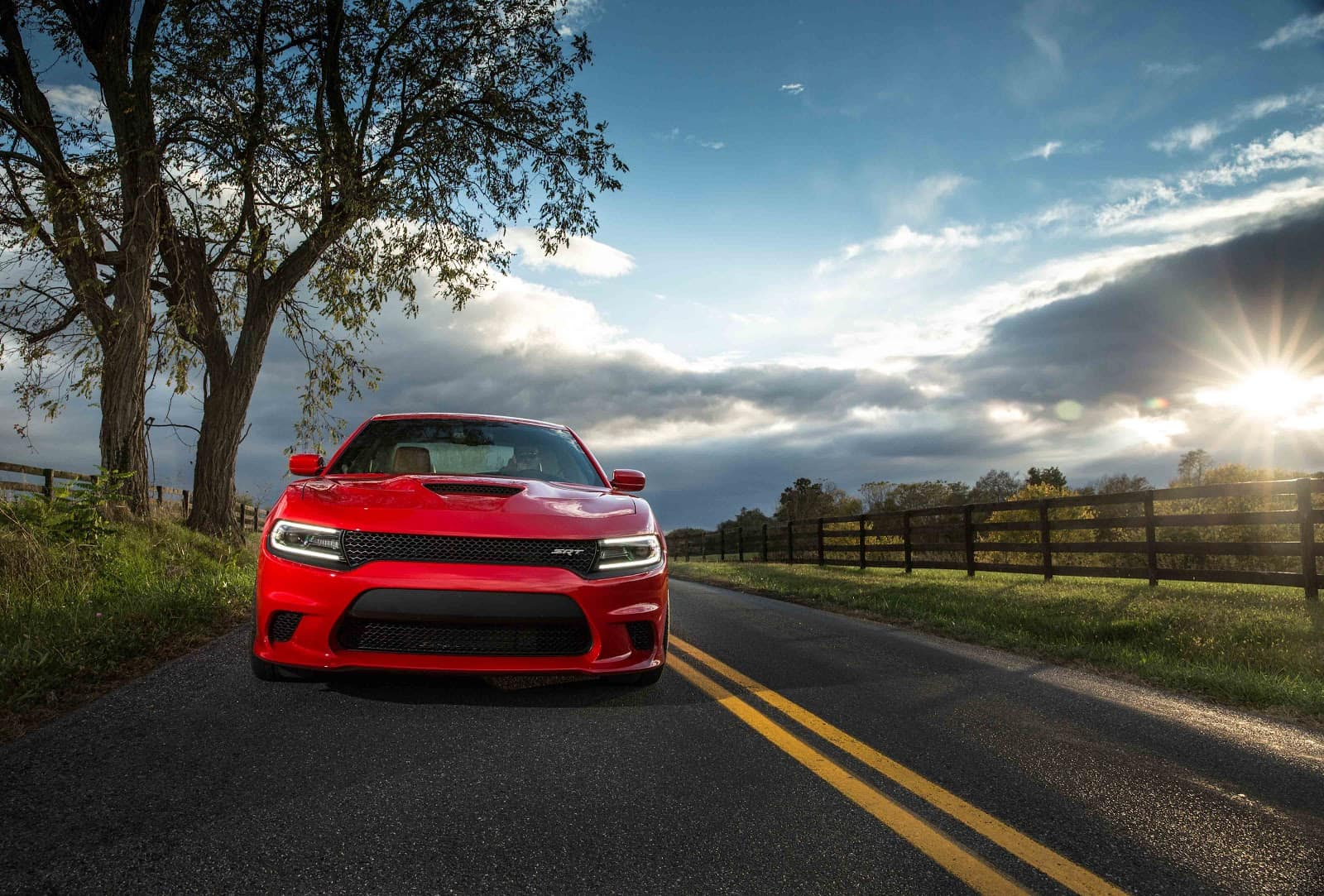 2019 Dodge Charger in Red Driving Down Country Road with Fields of Green on both sides