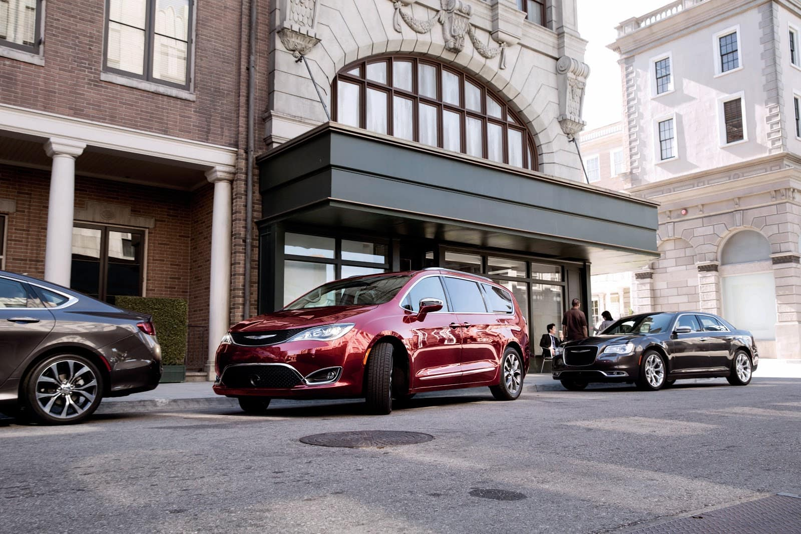 2019 Red Chrysler Pacifica Parallell Parked in front of Brick Building Among Other Cars