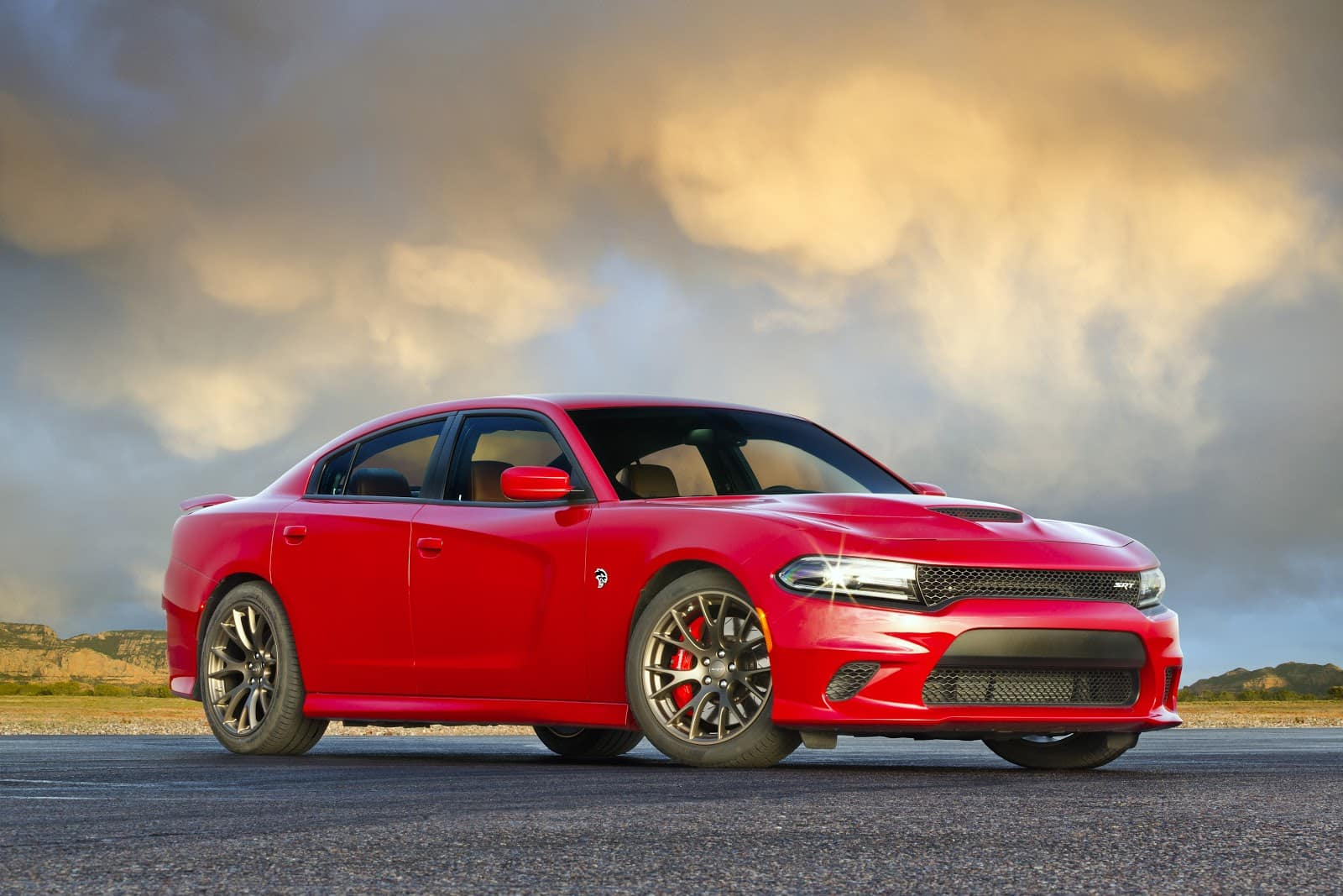 2019 Red Dodge Charger parked sideways on asphalt with sky in background