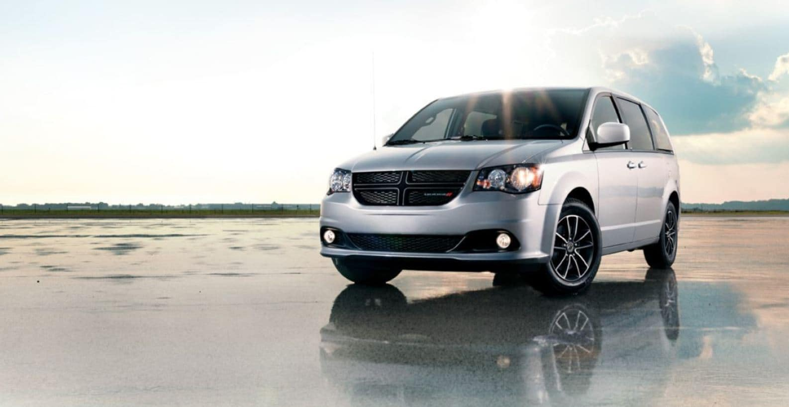 2019 dodge grand caravan with headlights on in sunny day on rainy pavement and reflection of vehicle showing in pavement