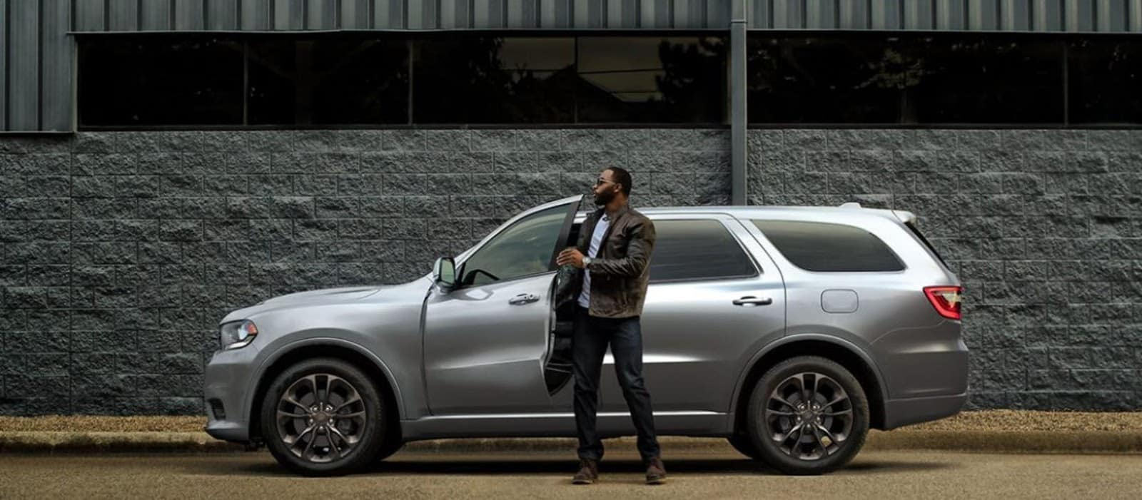 2019 silver dodge durango against dark gray wall on brown road with man in leather jacket and sunglasses stepping out of it holding door