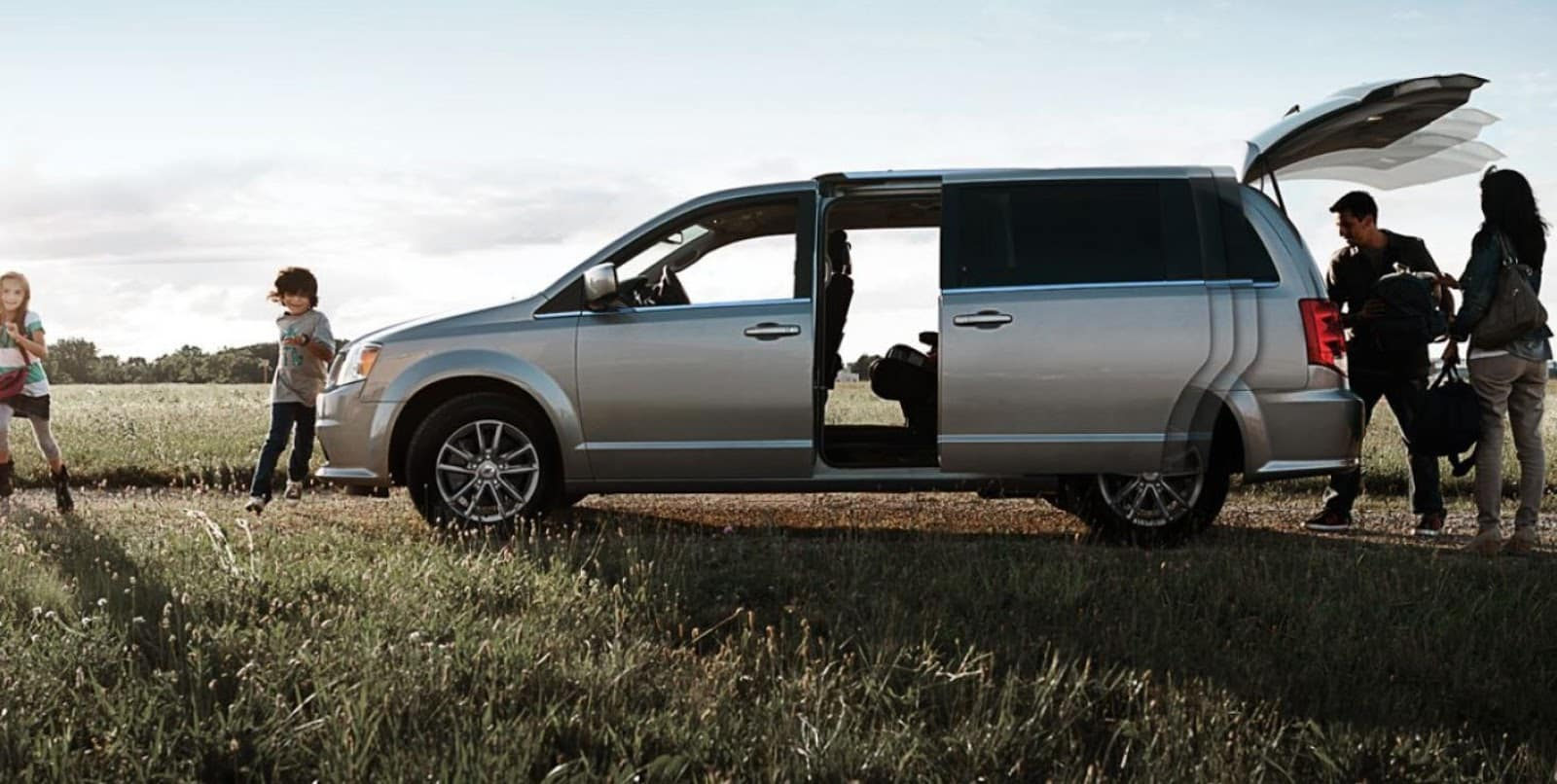 Kids Running in Field with Family around 2019 Silver Dodge Grand Caravan