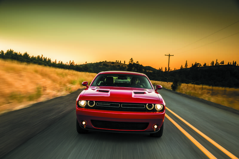 Red Dodge Challenger Driving Along Golden Fields
