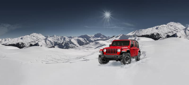 Red Jeep Wrangler in snow on mountainside