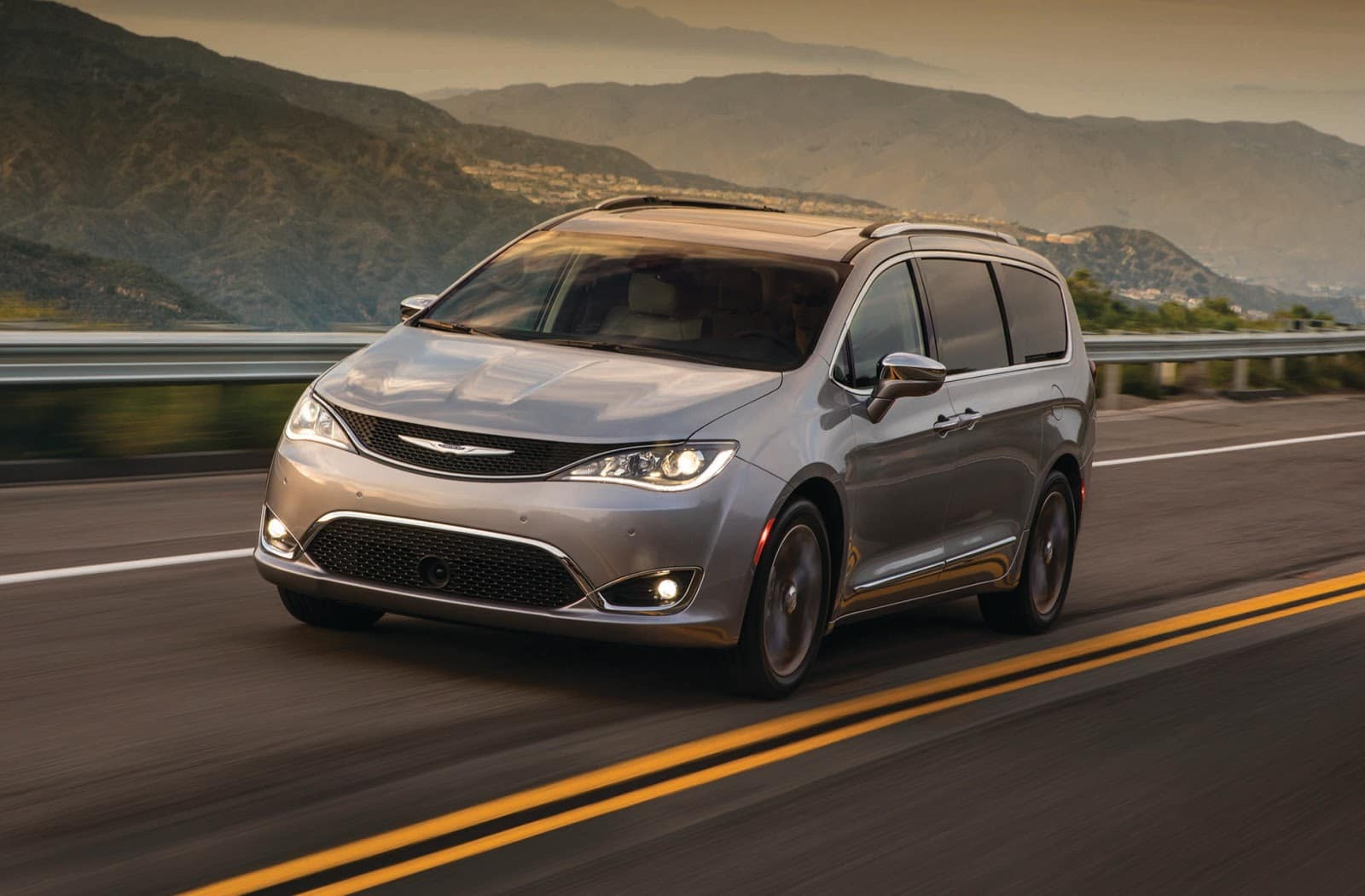 Silver 2019 Chrysler Pacifica Driving on Highway with Mountains in Background