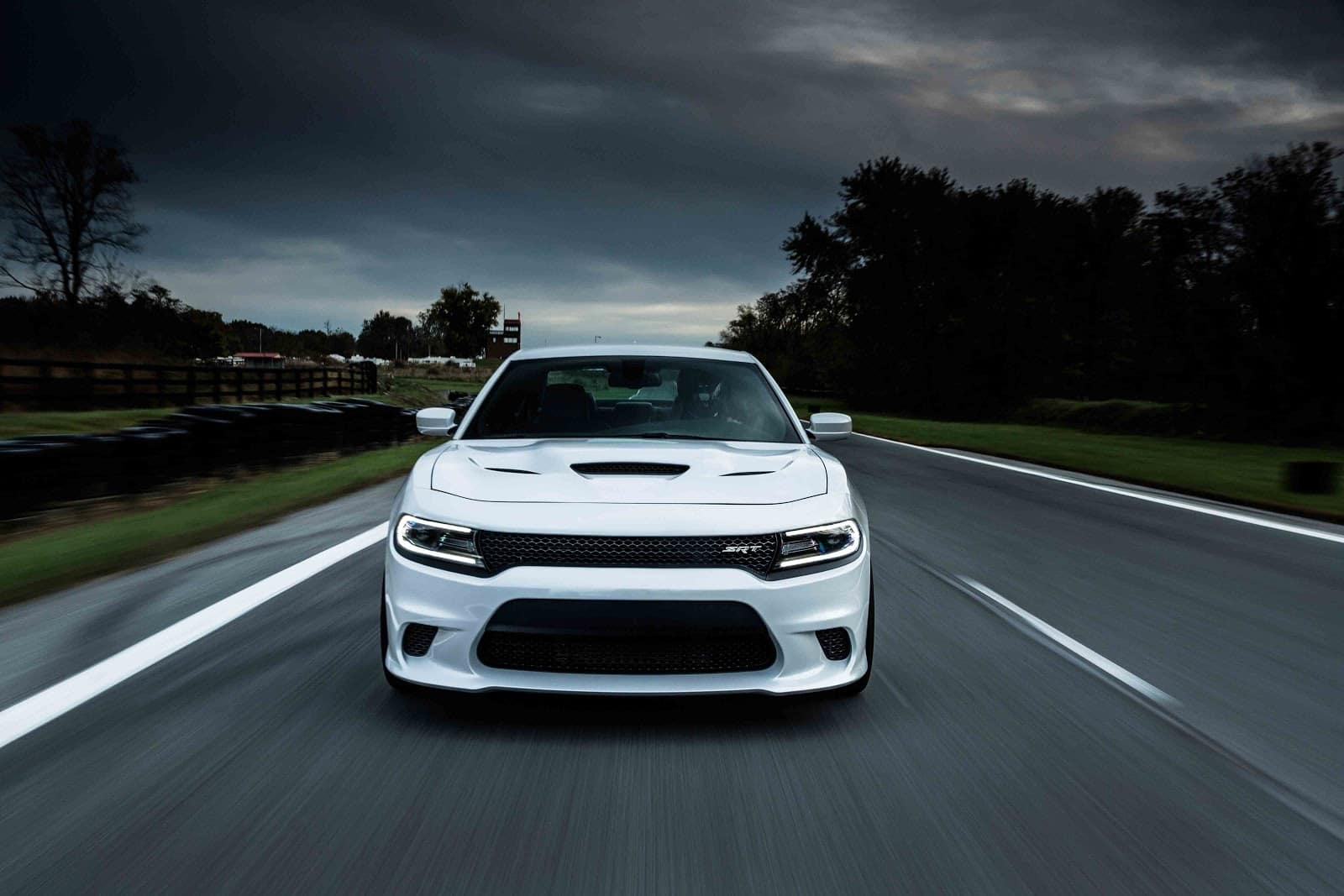 White 2019 Dodge Charger SRT driving down highway with storm clouds above and fields on either side of road