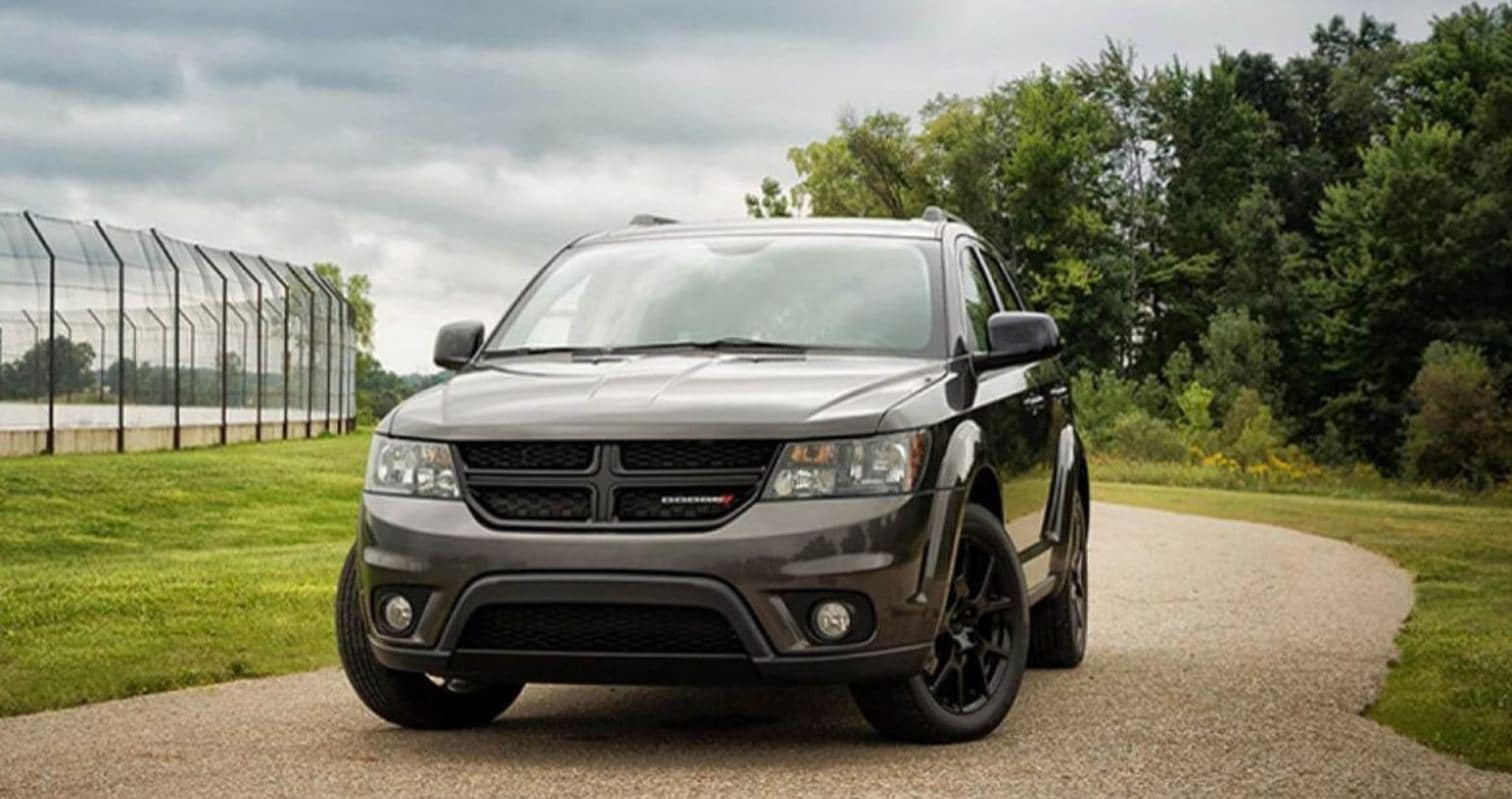 black dodge journey with black rims on narrow gravel road surrounded by a field with a sports court to the left and a forest to the right