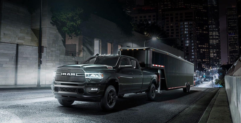 black ram 2500 towing black trailer on dark street at night in city