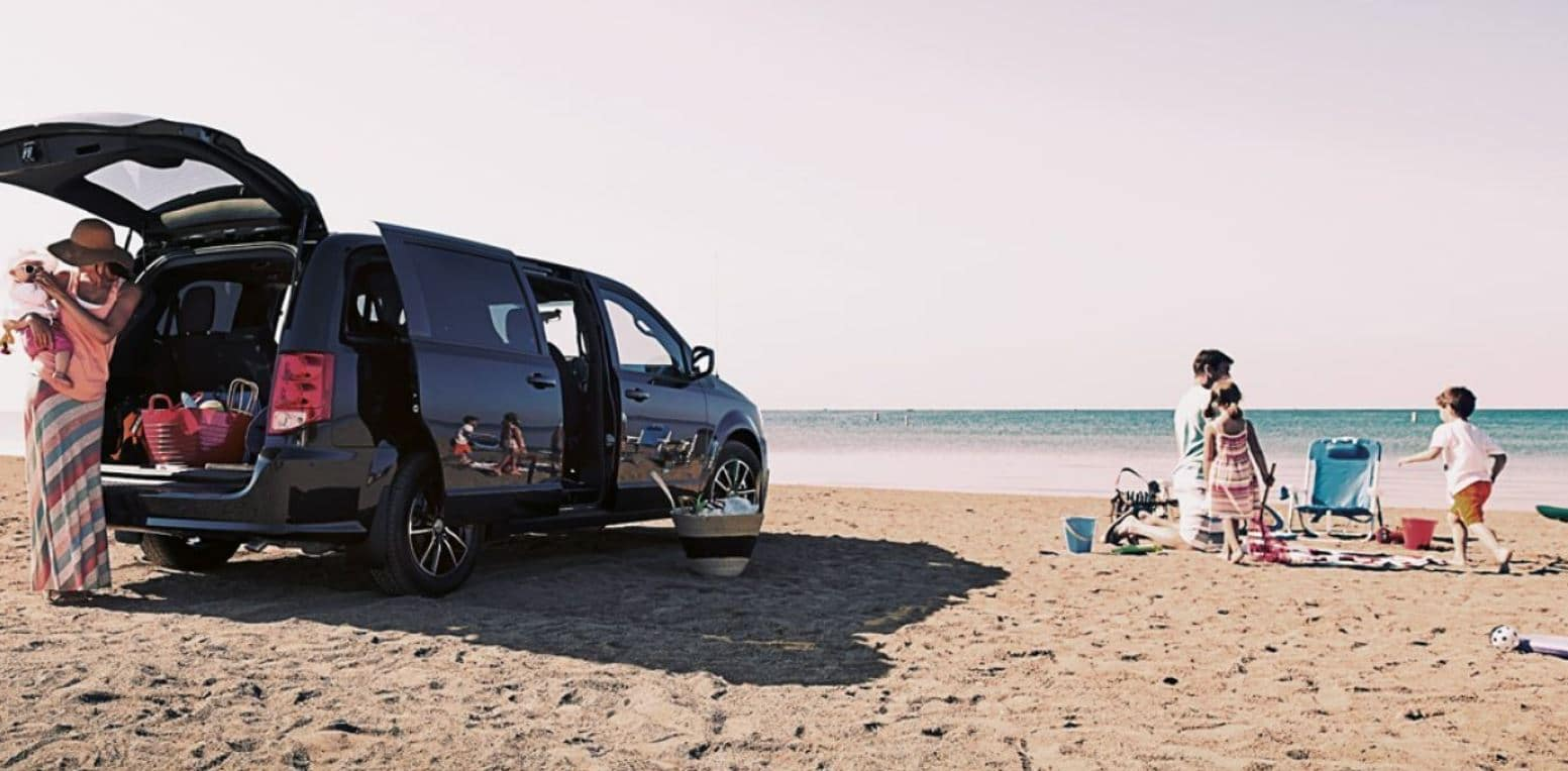 family at the beach with their 2019 dodge grand caravan on the sand while mom holds infant and dad is playing with toddler aged son and daughter