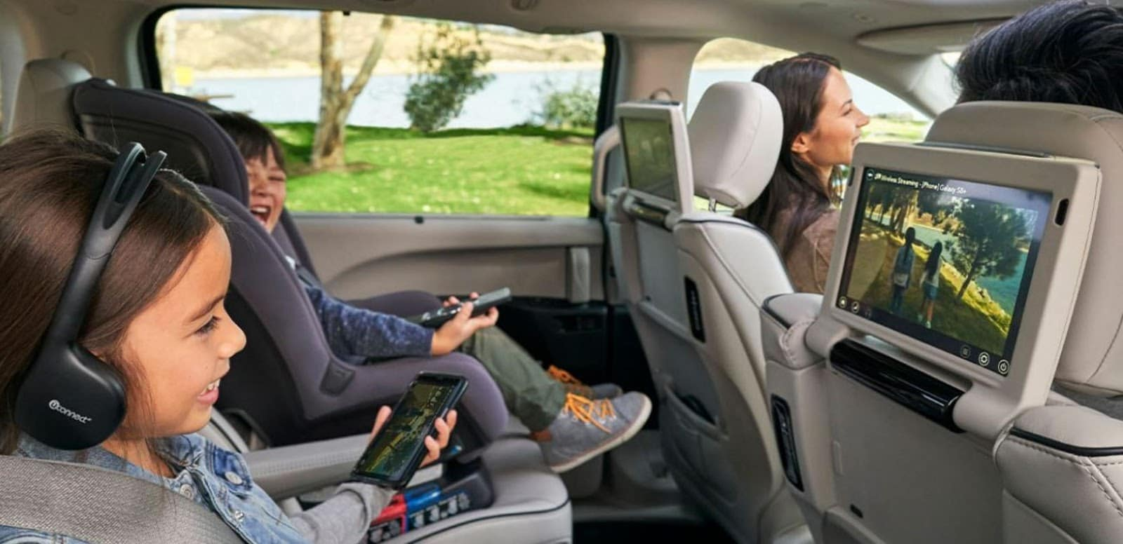 family enjoying technological features of chrysler pacifica
