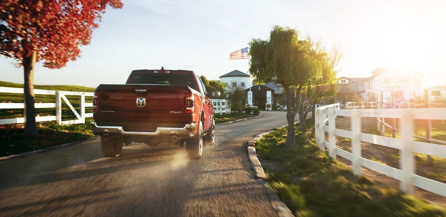 2019 ram 1500 red driving on gravel road with white picket fence on either side