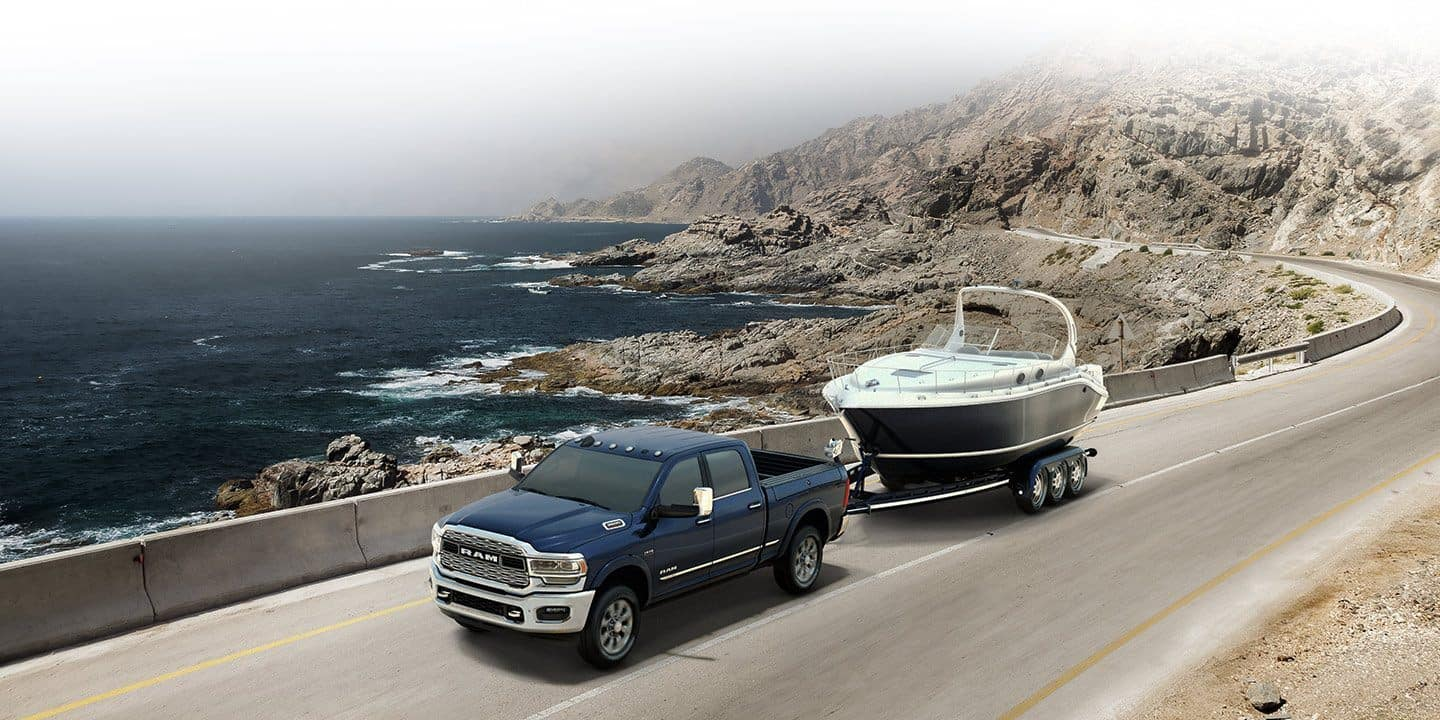 ram 3500 fr towing a boat next to the ocean