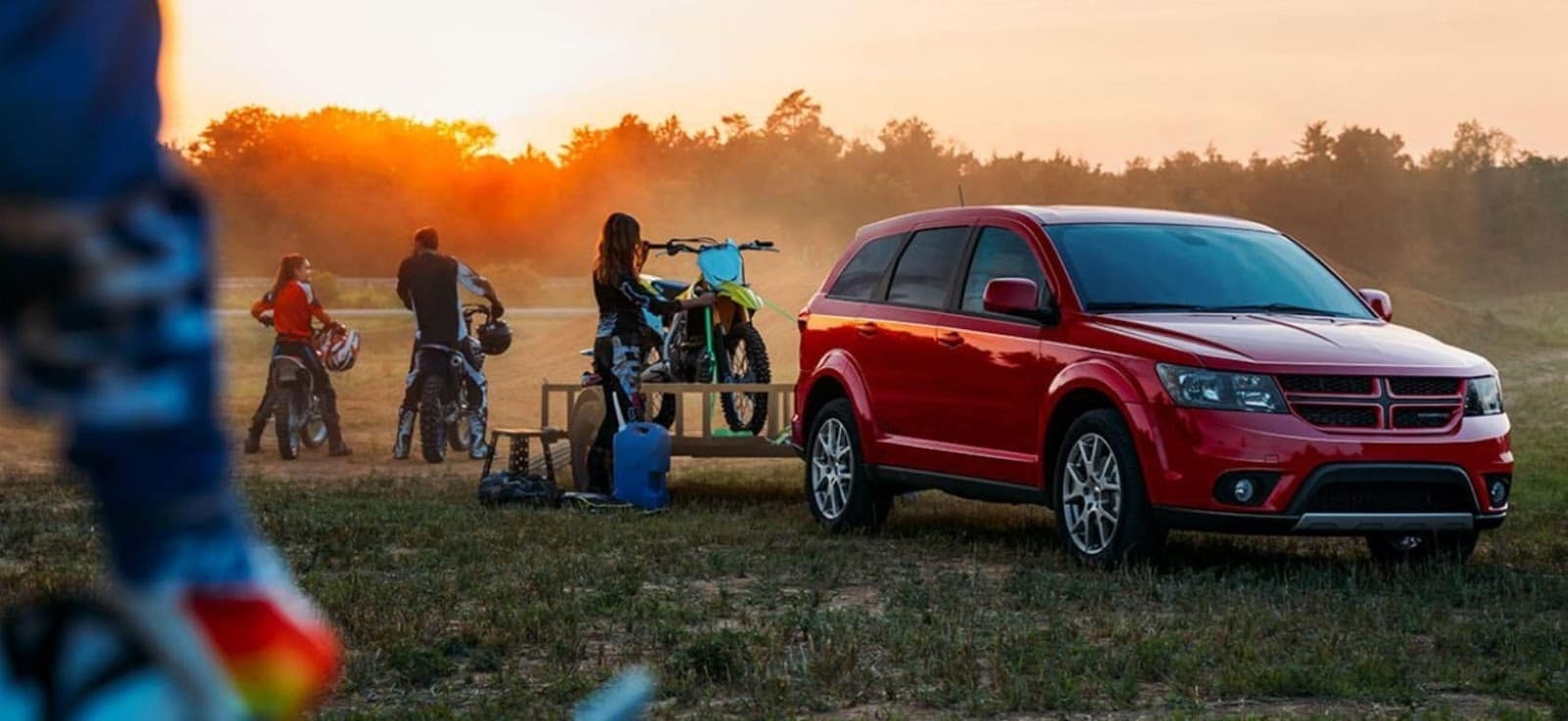 red dodge journey at sunset towing dirtbikes of family in a lush green field with family out of focus