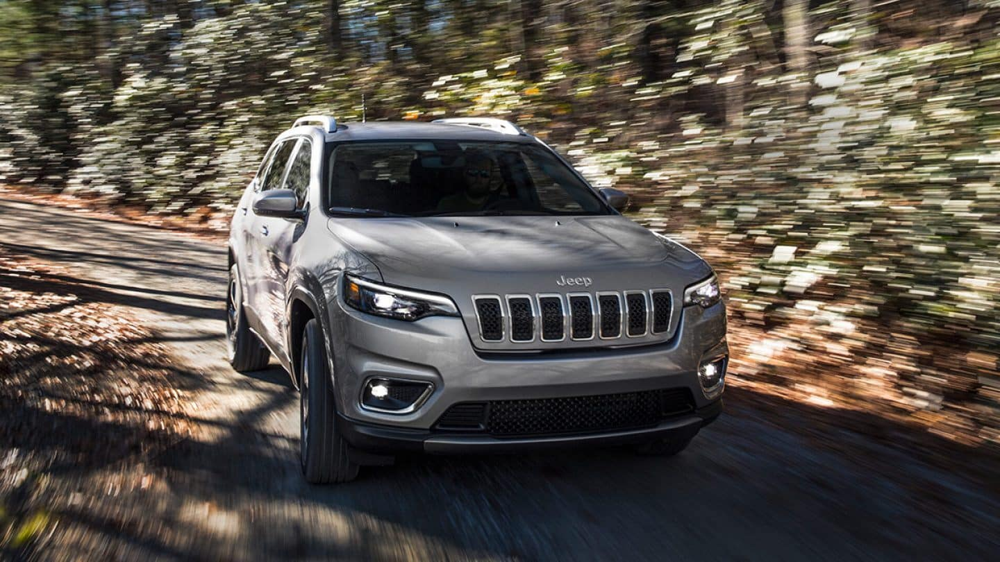 silver 2019 jeep cherokee driving on dirt road at fast speed
