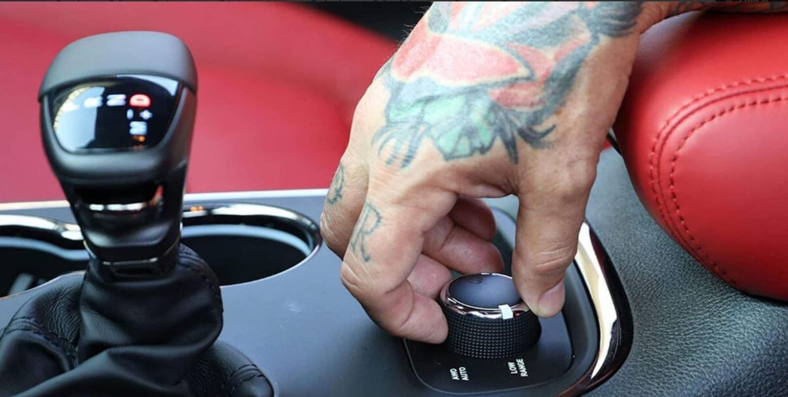 tattooed hand holding knob on 2019 dodge durango srt against bright red interior