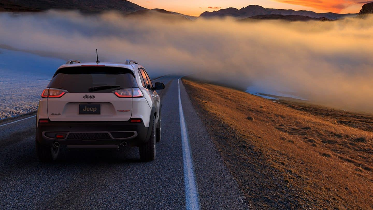 white 2019 jeep cherokee driving through cloud on isolated round surrounded by scenery