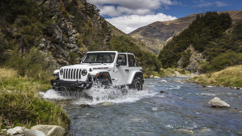 white 2019 jeep wrangler going thru water inbetween mountains