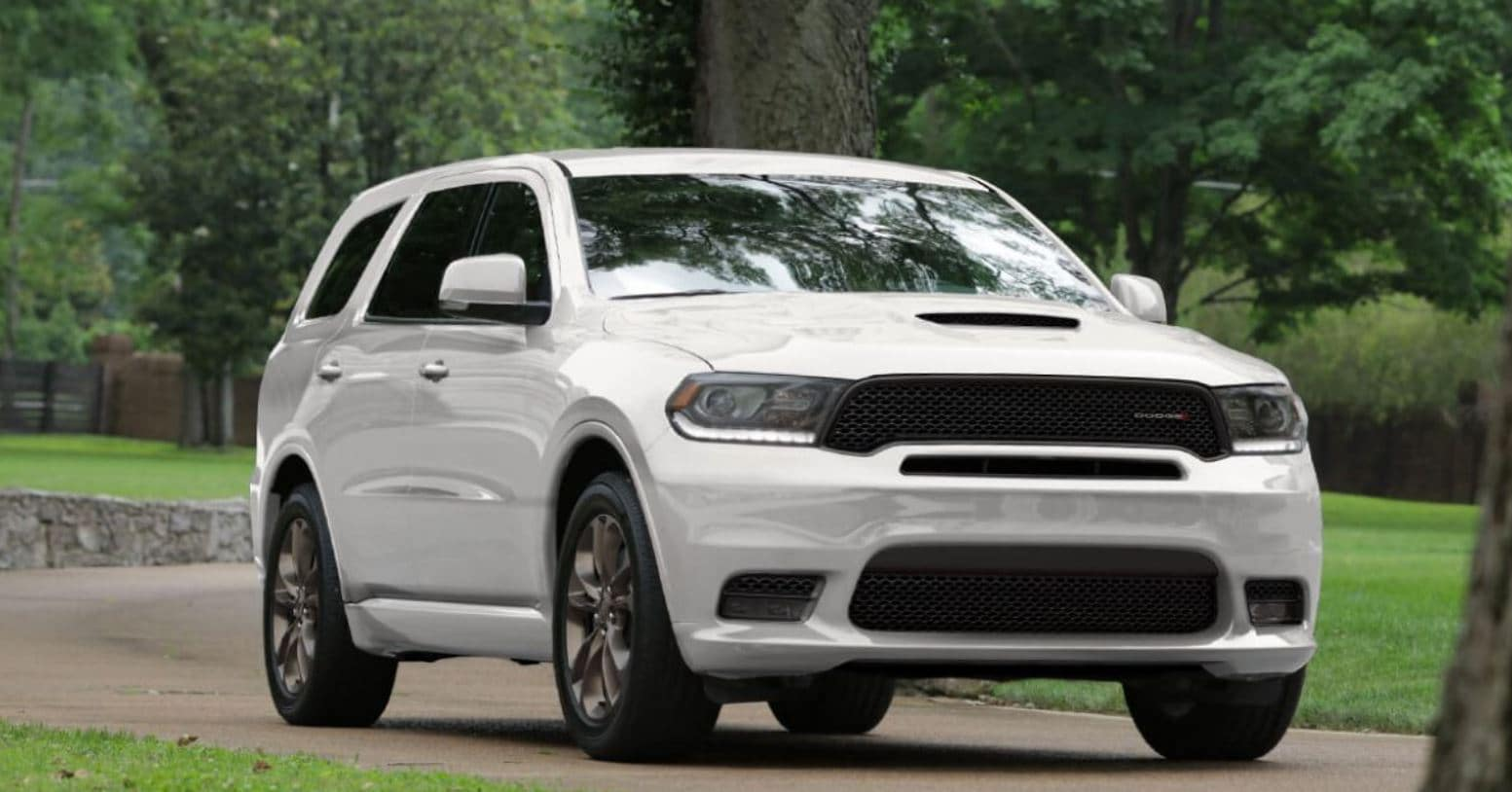 white dodge durango on narrow windy road surrounded by trees and cut grass on either side