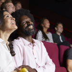 Couples sitting in red theater seats watching a movie and eating popcorn