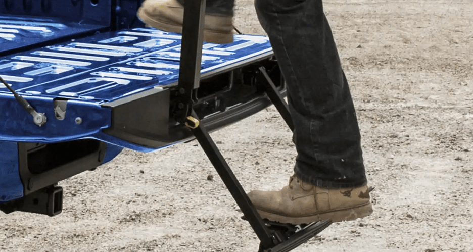 Man stepping up onto tailgate step on truck bed with tailgate lift assist