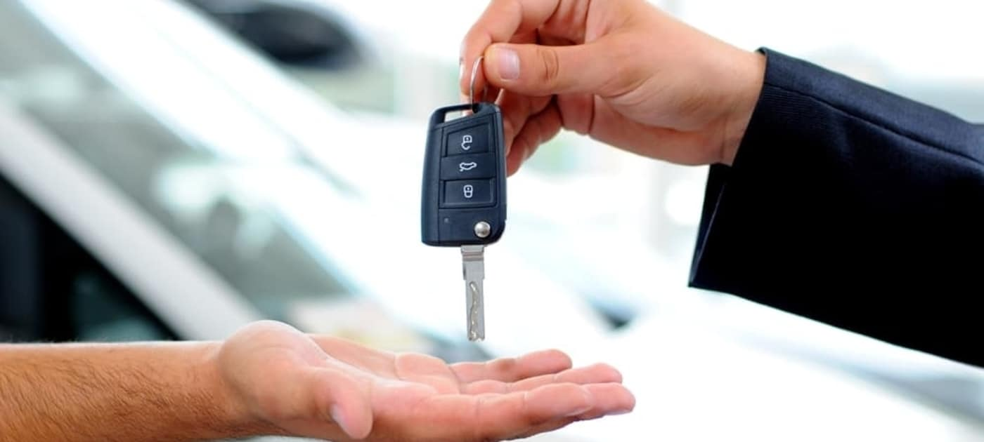 Car salesman passing car key to consumer