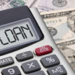 """Calculator on top of money money with word """"Loan"""" spelled out in it"""