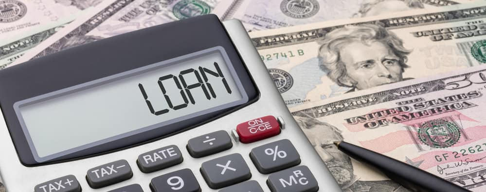 "Calculator on top of money money with word ""Loan"" spelled out in it"