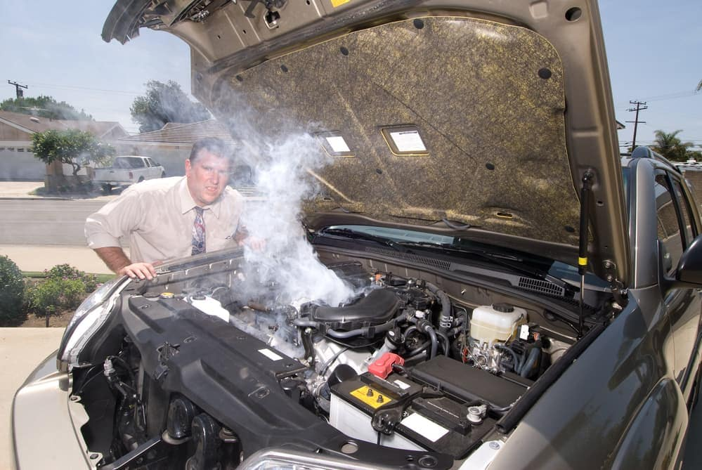 Man looks on as his car engine overheats