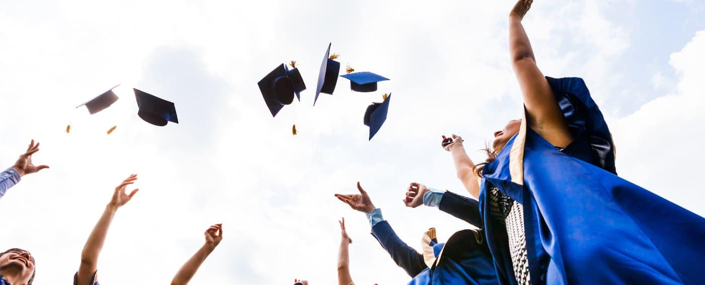 college graduates throw cap in air