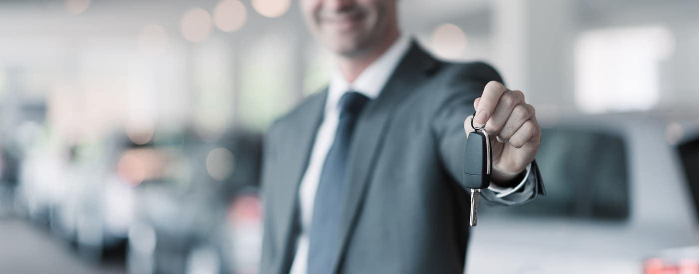 car salesman giving new car key