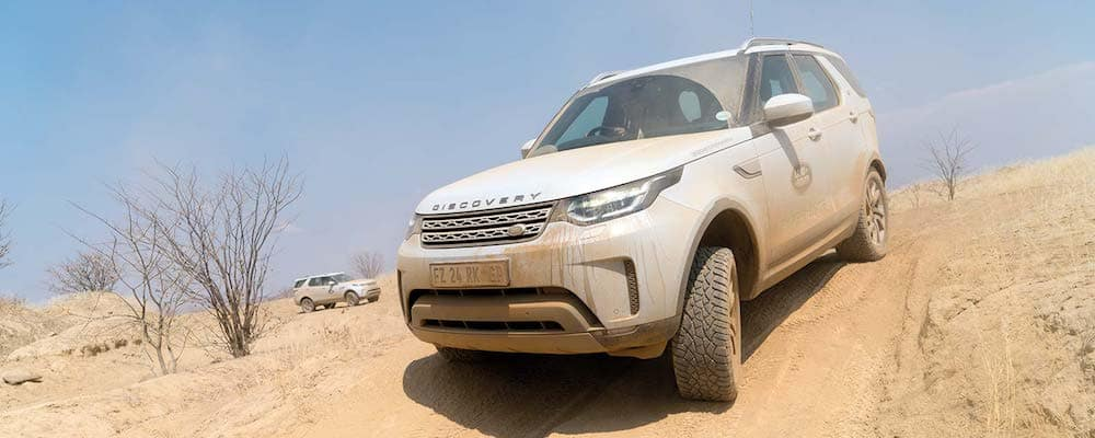 Land Rover Discovery driving on dusty desert hill with another Land Rover in background