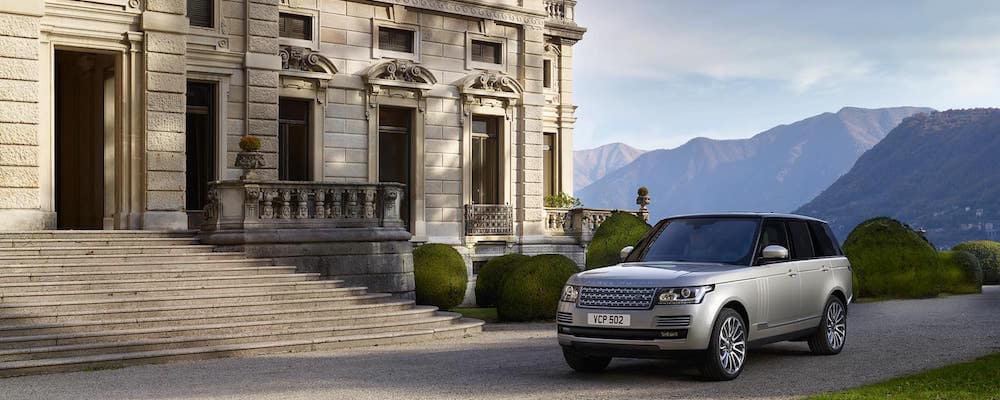 Silver Range Rover HSE parked in front of a large building with mountains in the background