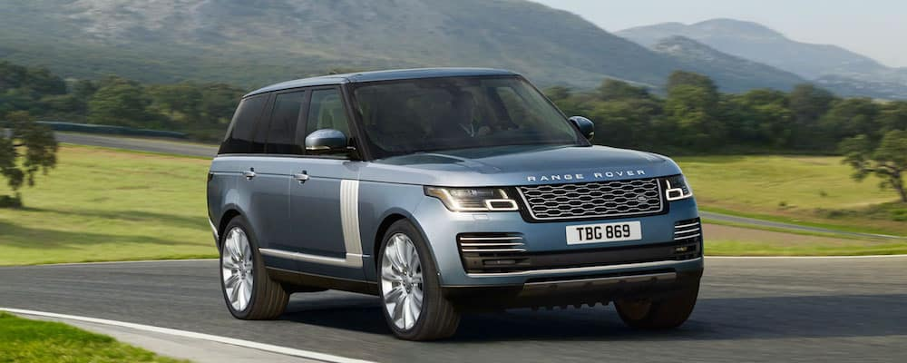Blue Range Rover driving down a scenic road