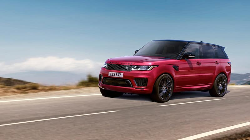 Red Range Rover Sport driving on a highway with a clear blue sky in the background