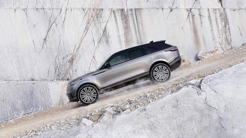 side view of Gray Range Rover Velar driving down a path on a gray mountain