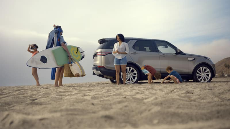 Family on a beach near their silver Land Rover Discovery